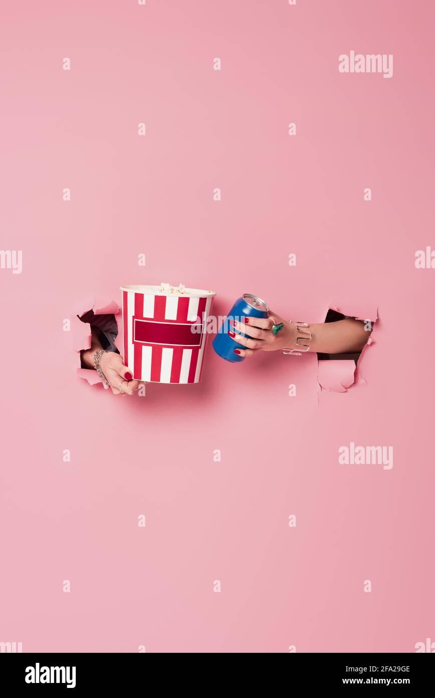 Vista recortada de la mujer que sostiene la bebida enlatada y palomitas adentro agujeros de fondo rosa Foto de stock