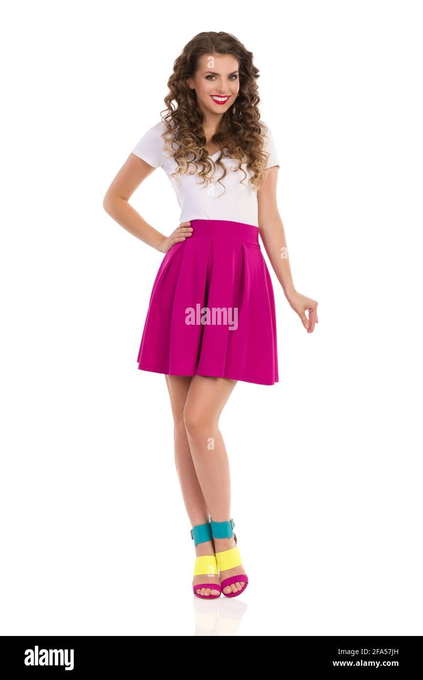 Hermosa mujer joven sonriente con coloridos talones altos, falda mini rosa y top blanco está de pie y mirando la cámara. Vista frontal. Estudio completo Foto de stock