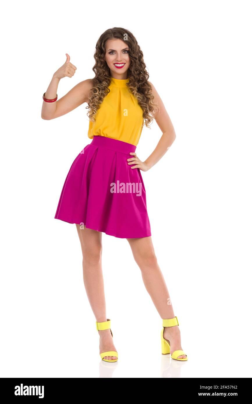Hermosa mujer joven en los talones altos vibrantes, falda mini rosa y la parte superior amarilla está de pie, mostrando el pulgar hacia arriba y sonriendo. Vista frontal. Estudio completo Foto de stock