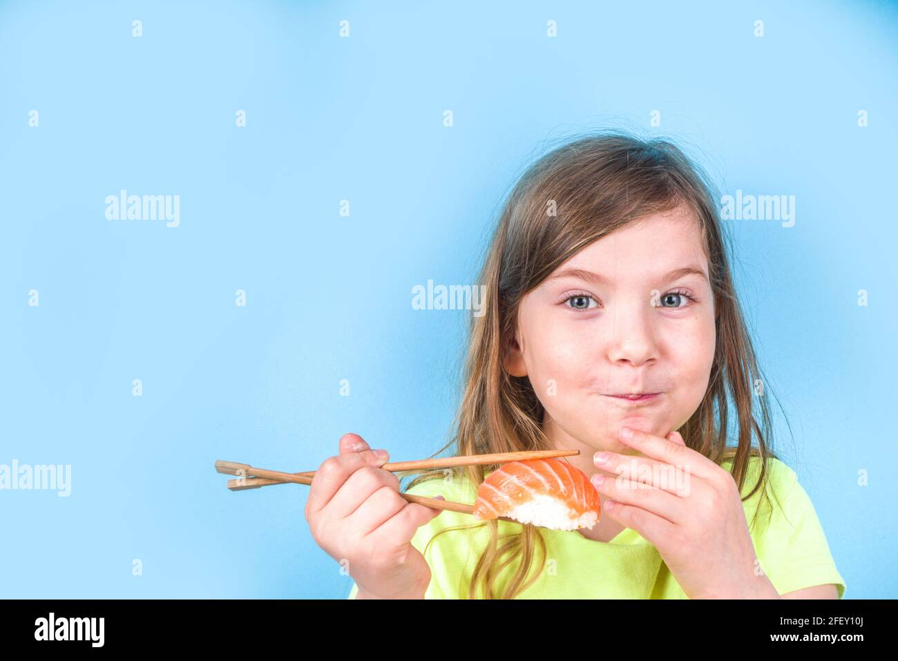 A la chica linda le gusta comer sushi. Alegre niña de preescolar rubia caucásica divertida con varios rollos de sushi y palillos. Sobre fondo azul brillante Foto de stock