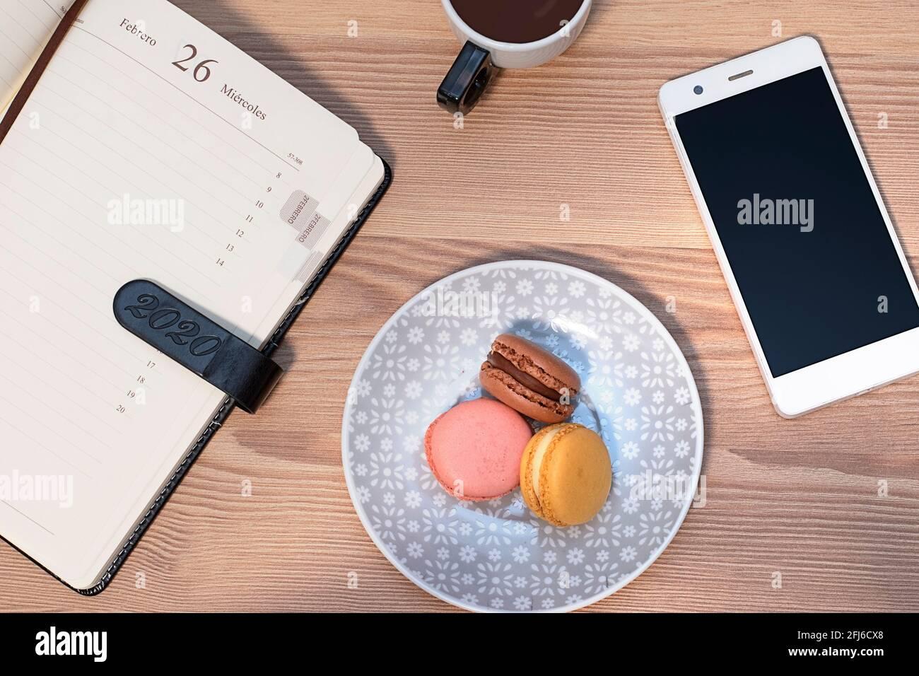 foto cenital de sabrosas macarrones, taza de café, diario y teléfono móvil sobre una mesa de madera Foto de stock