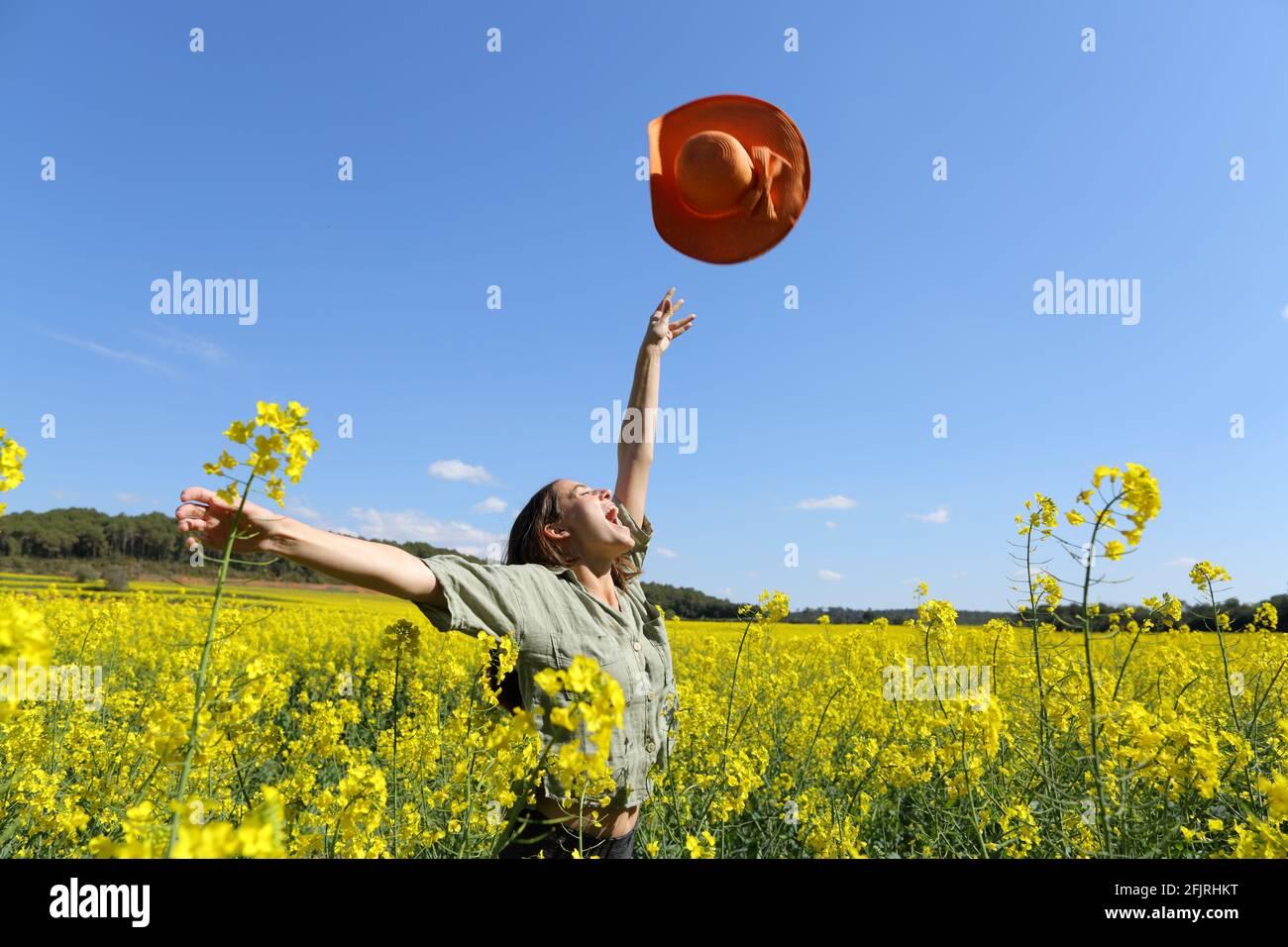 Mujer feliz lanzando pamela celebrando vacaciones en un amarillo florecido campo en primavera Foto de stock
