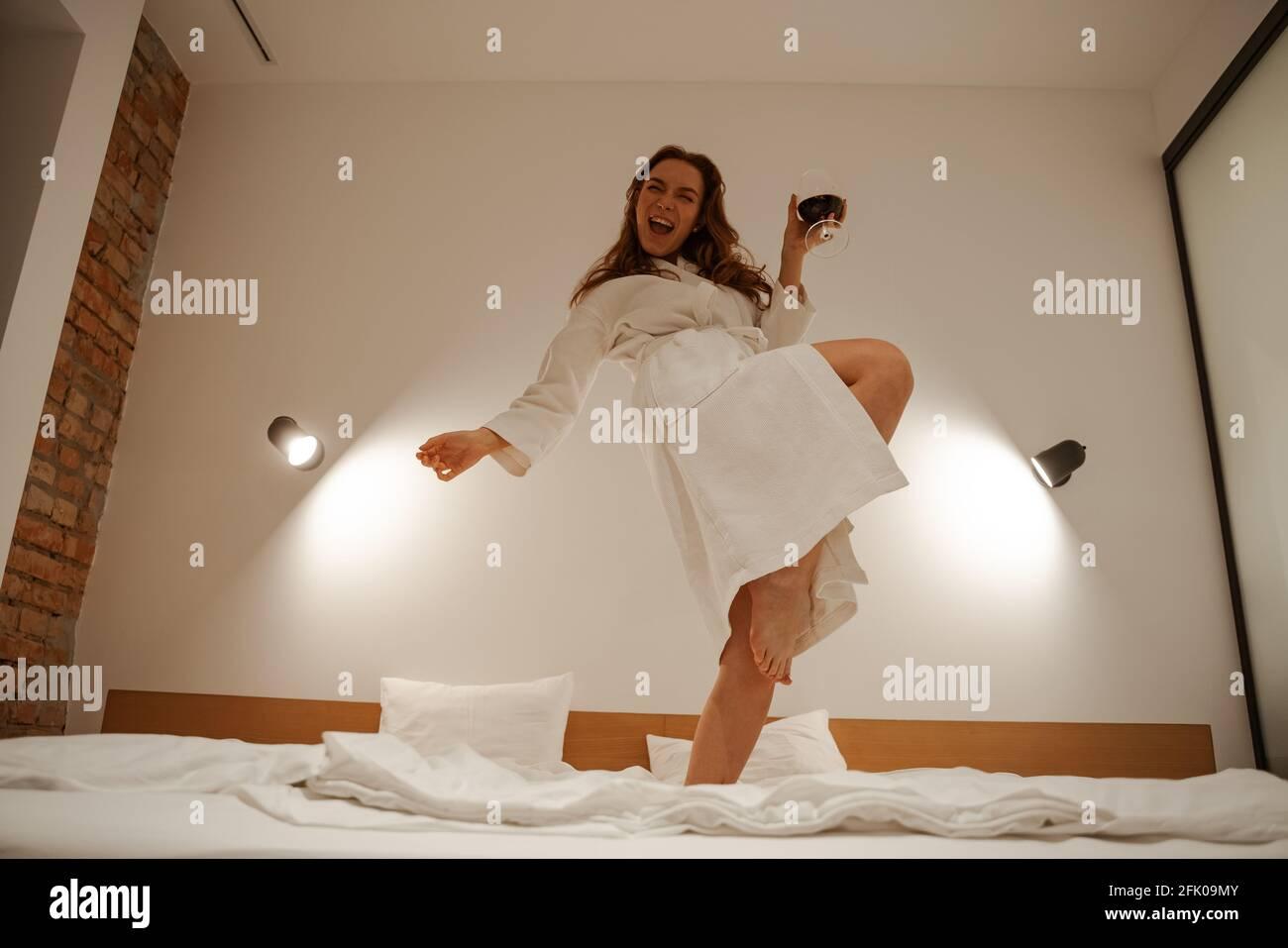Mujer joven de pelo rojo con una toalla en la cabeza y un albornoz blanco saltando y divirtiéndose en la cama. Ambiente alegre en la habitación del hotel. Jóvenes y. Foto de stock