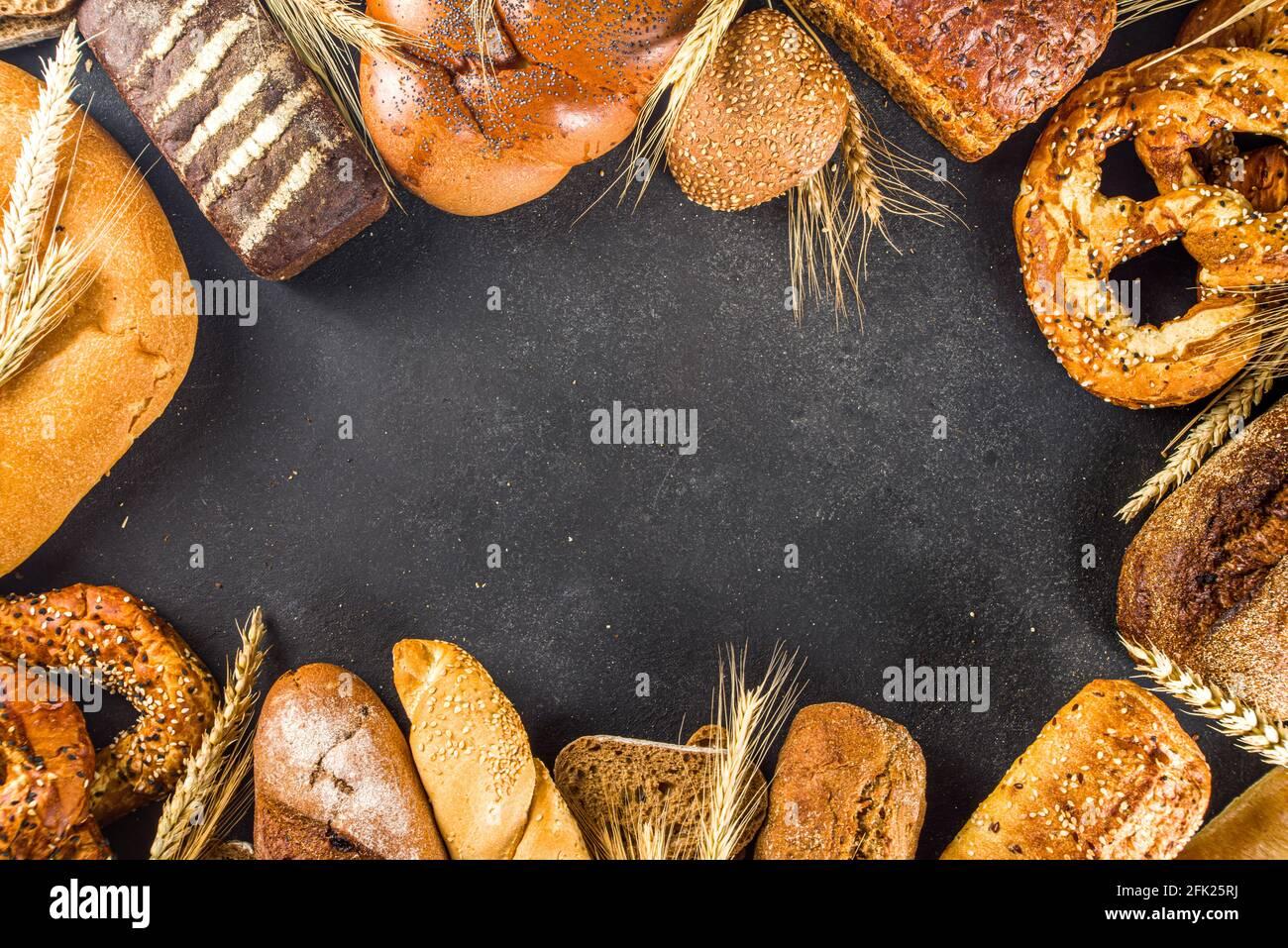 Surtido de varios deliciosos panes recién horneados, sobre fondo de hormigón negro vista superior espacio de copia Foto de stock