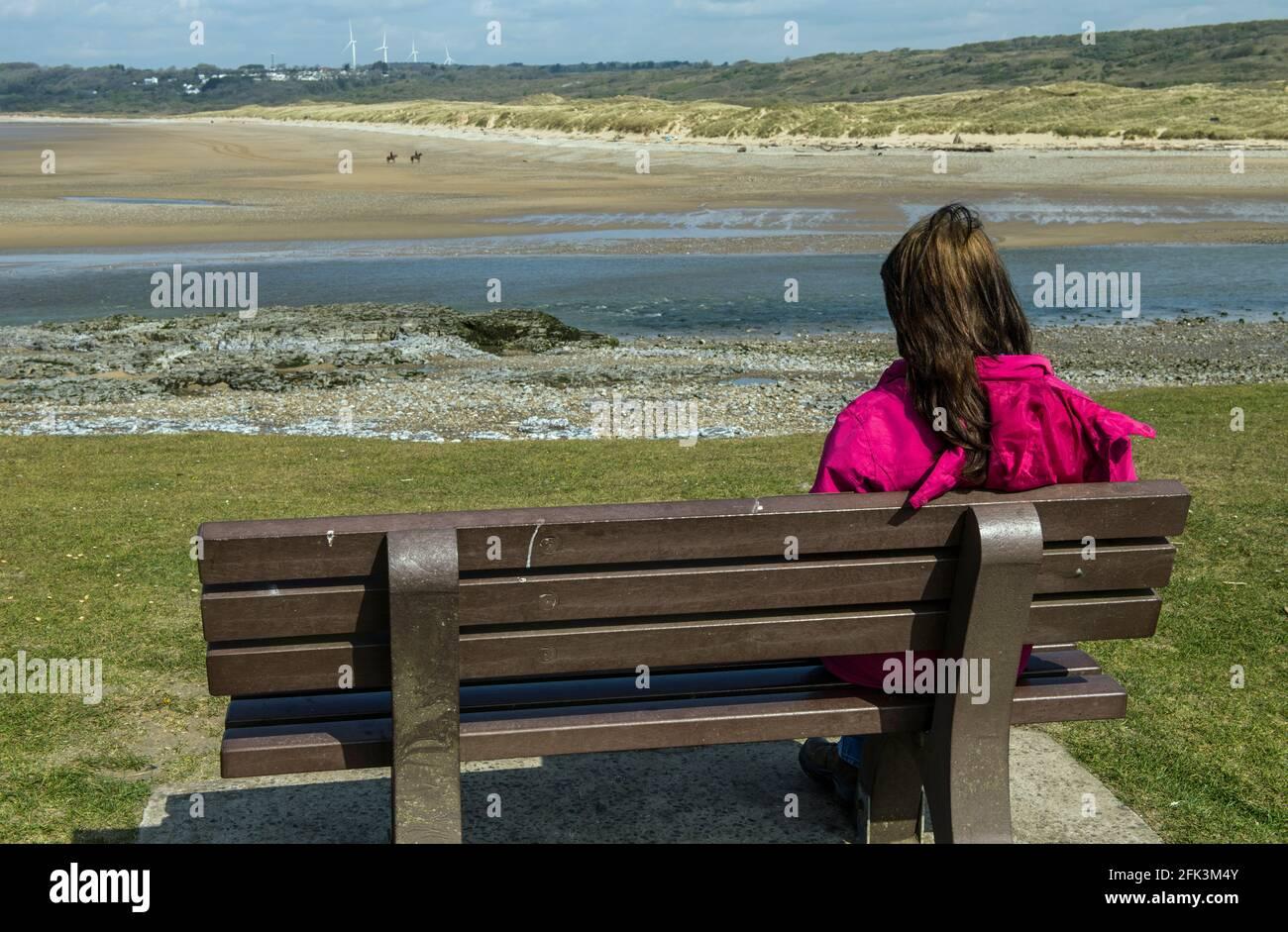 Señora mirando al otro lado del estuario del río Ogmore en Ogmore by Sea en la Costa de la Herencia de Glamourgan, al sur de Gales Foto de stock