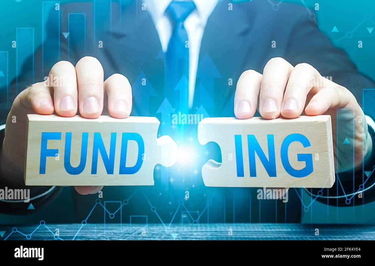Businessman conecta rompecabezas con la palabra financiación. Invertir en un proyecto empresarial, recaudar fondos. Proporcionar recursos financieros. Crédito, donaciones, Foto de stock