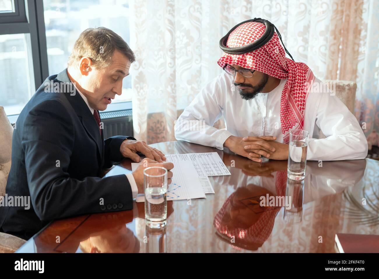 Dos delegados masculinos sentados en una mesa y discutiendo documentos en la reunión de trabajo Foto de stock