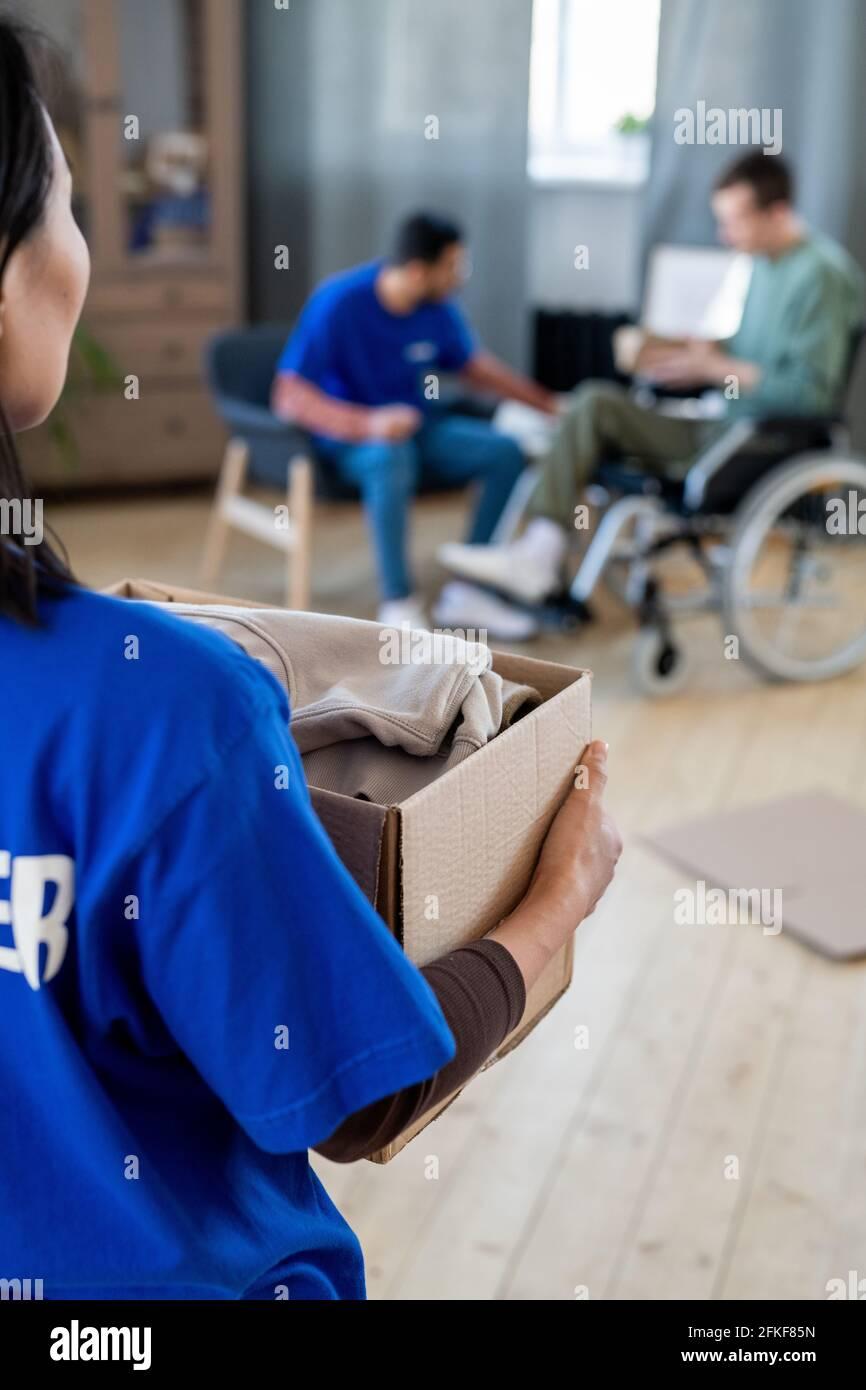 Mujer voluntaria llevando la caja con ropa contra el hombre en un silla de ruedas y su colega Foto de stock