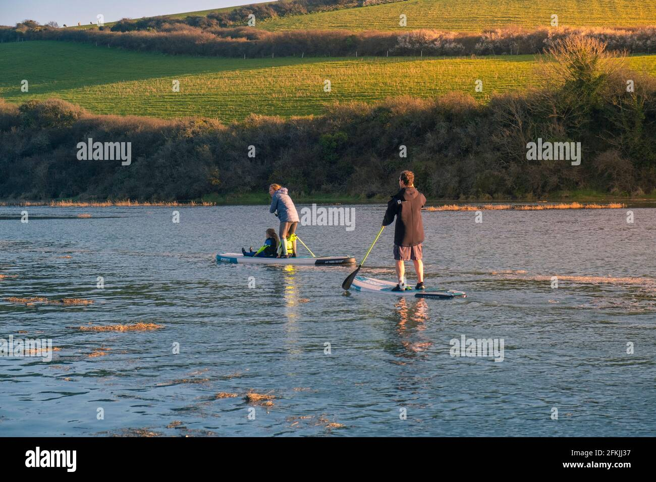Una familia de turistas que se divierten remando sus tablas de paddleboard de pie en marea alta en el río Gannel en Newquay en Cornwall. Foto de stock