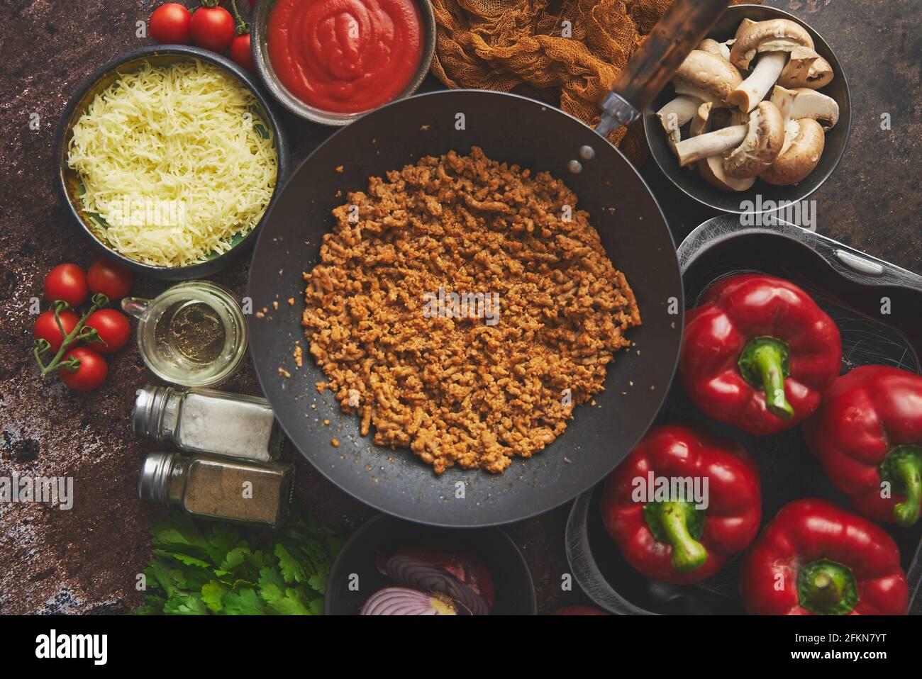 Ingredientes en una mesa preparada para el relleno de pimientos. Pimientos rojos, carne picada, queso Foto de stock