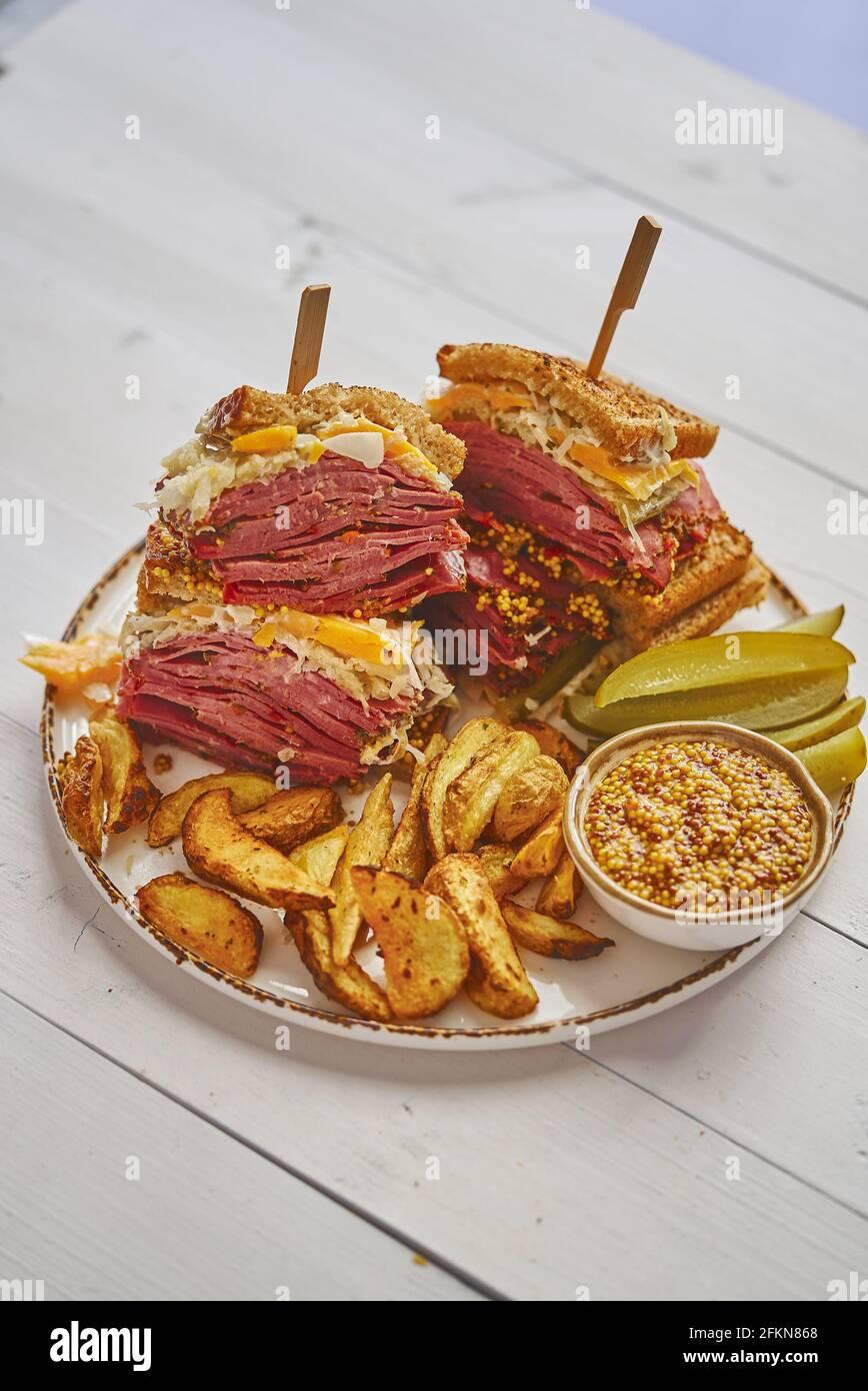Sabrosos sándwiches de reuben a la parrilla de gran lujo con carne de pastrami y queso cheddar Foto de stock