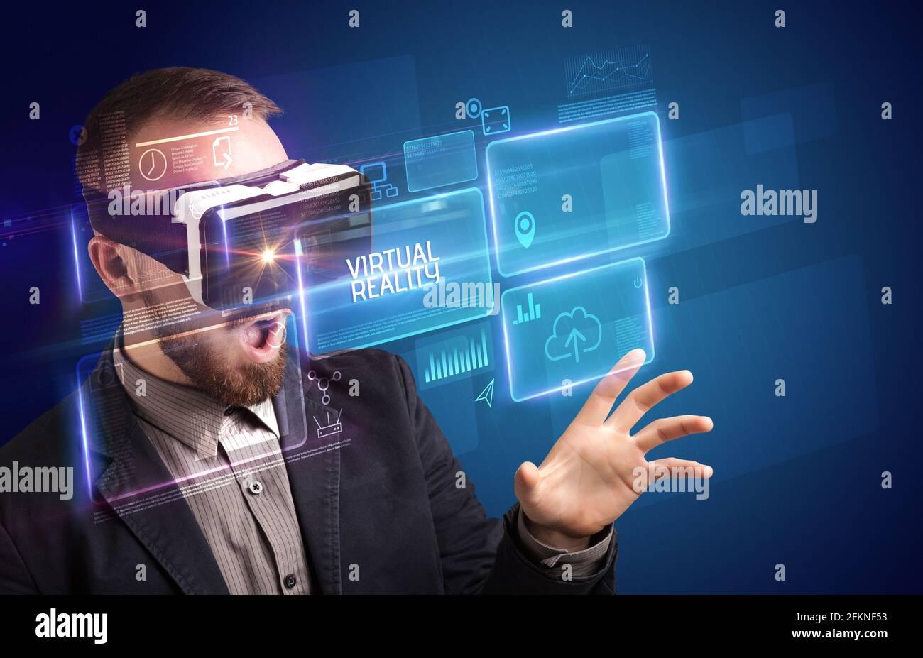 Hombre de negocios mirando a través de gafas de realidad Virtual, concepto tecnológico Foto de stock