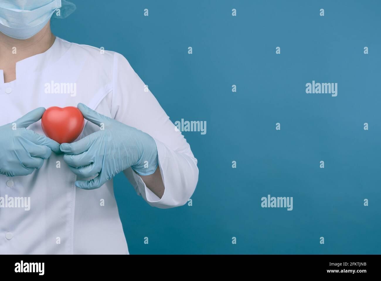 médico femenino en un abrigo blanco, una máscara se levanta y sostiene un corazón rojo sobre un fondo azul, el concepto de donación y amabilidad, espacio de copia. Foto de stock