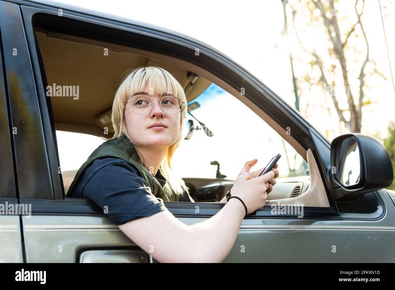 Adolescente seguro sosteniendo el teléfono móvil que se inclina fuera de la ventana del pasajero de coche Foto de stock