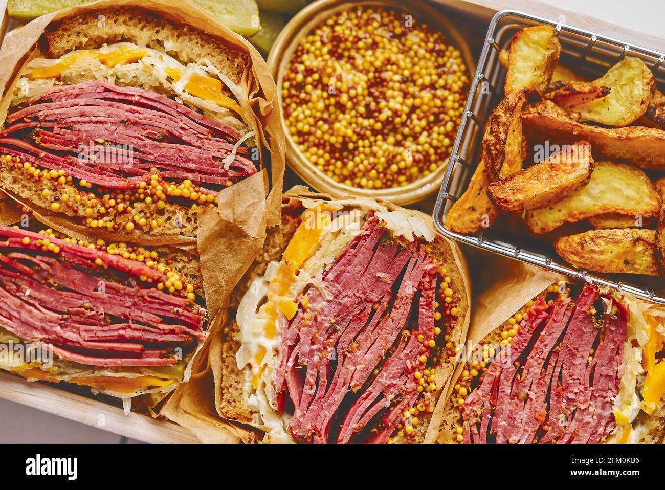 Enormes sándwiches con carne de pastami en caja de madera. Servido con patatas al horno, encurtidos Foto de stock