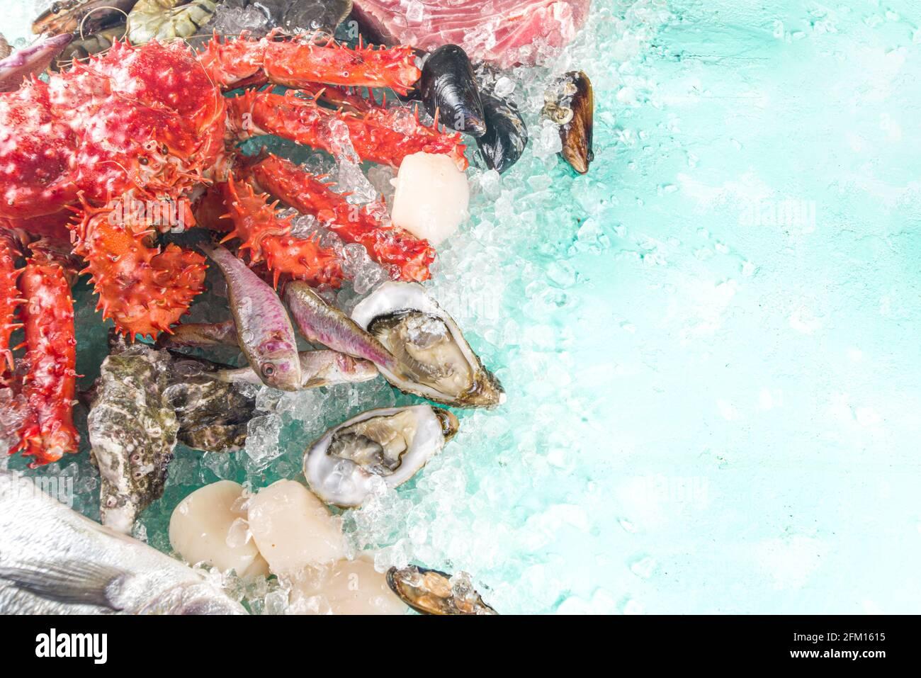 Conjunto de varios mariscos frescos crudos - pulpo, cangrejo, calamares, langostinos, ostras, mejillones, salmón atún dorado pescado con especias de hierbas limón, azul claro Foto de stock