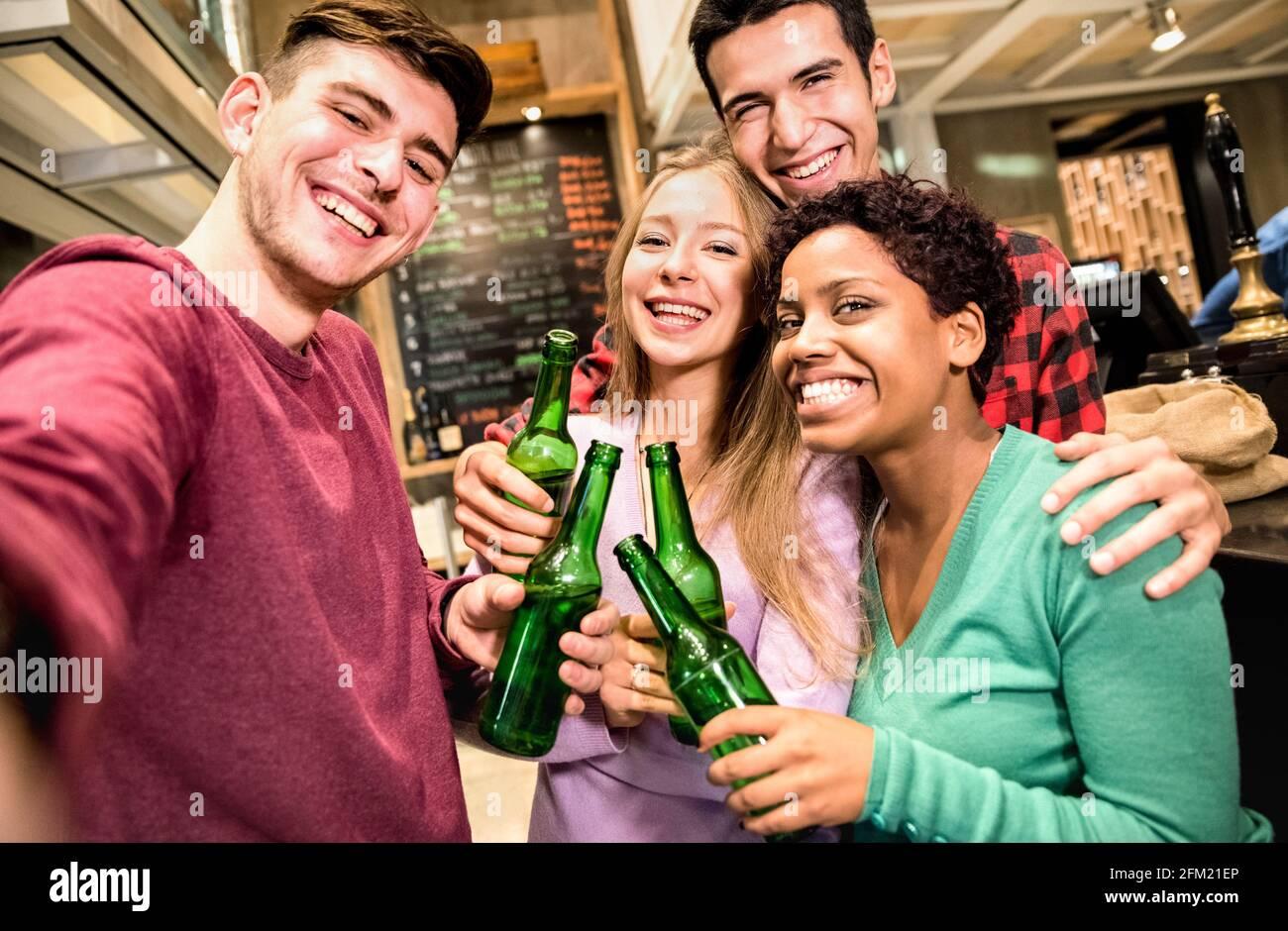 Amigos multirraciales tomando selfie y bebiendo cerveza en la cervecería de lujo Restaurante - Concepto de amistad con jóvenes que disfrutan del tiempo juntos Foto de stock