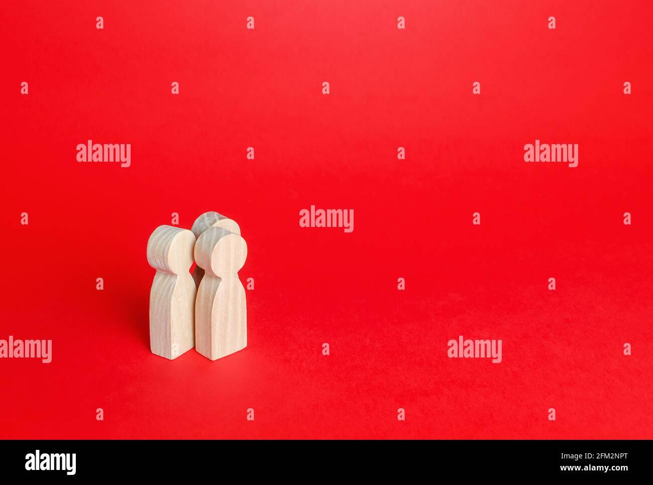 Tres figuras humanas sobre fondo rojo. Comunicación y discusión. Relaciones amistosas. Una reunión. Asistencia, cooperación y colaboración. PLA Foto de stock