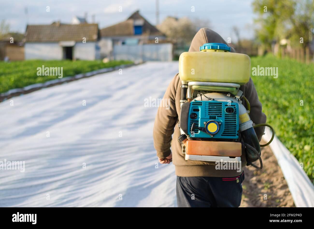 Un granjero con un rociador de niebla en su espalda camina a través del campo de la granja. Protección de plantas cultivadas contra insectos e infecciones fúngicas. El uso de Foto de stock