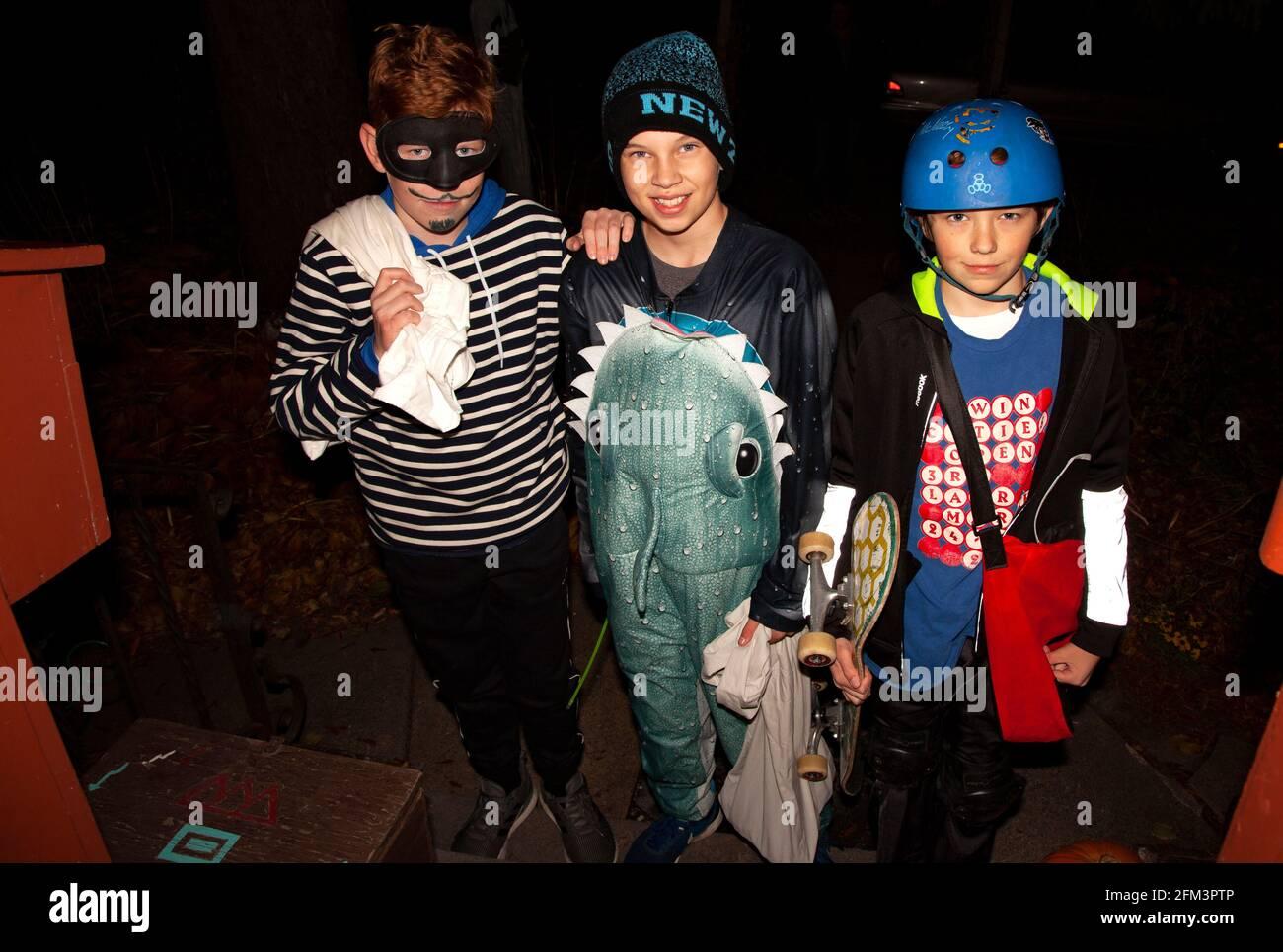 Truco de Halloween y tratadores disfrazados como un burglar de tiburón y skateboarder. St Paul Minnesota MN EE.UU Foto de stock