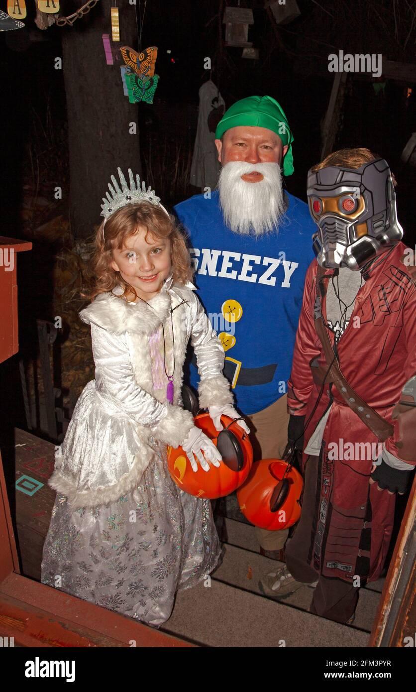 Truco de Halloween y tratantes con papá como Sneezy de los Siete Dwarfs, una princesa y Señor Estrella de Guardianes de la Galaxia. St Paul Minnesota MN EE.UU Foto de stock