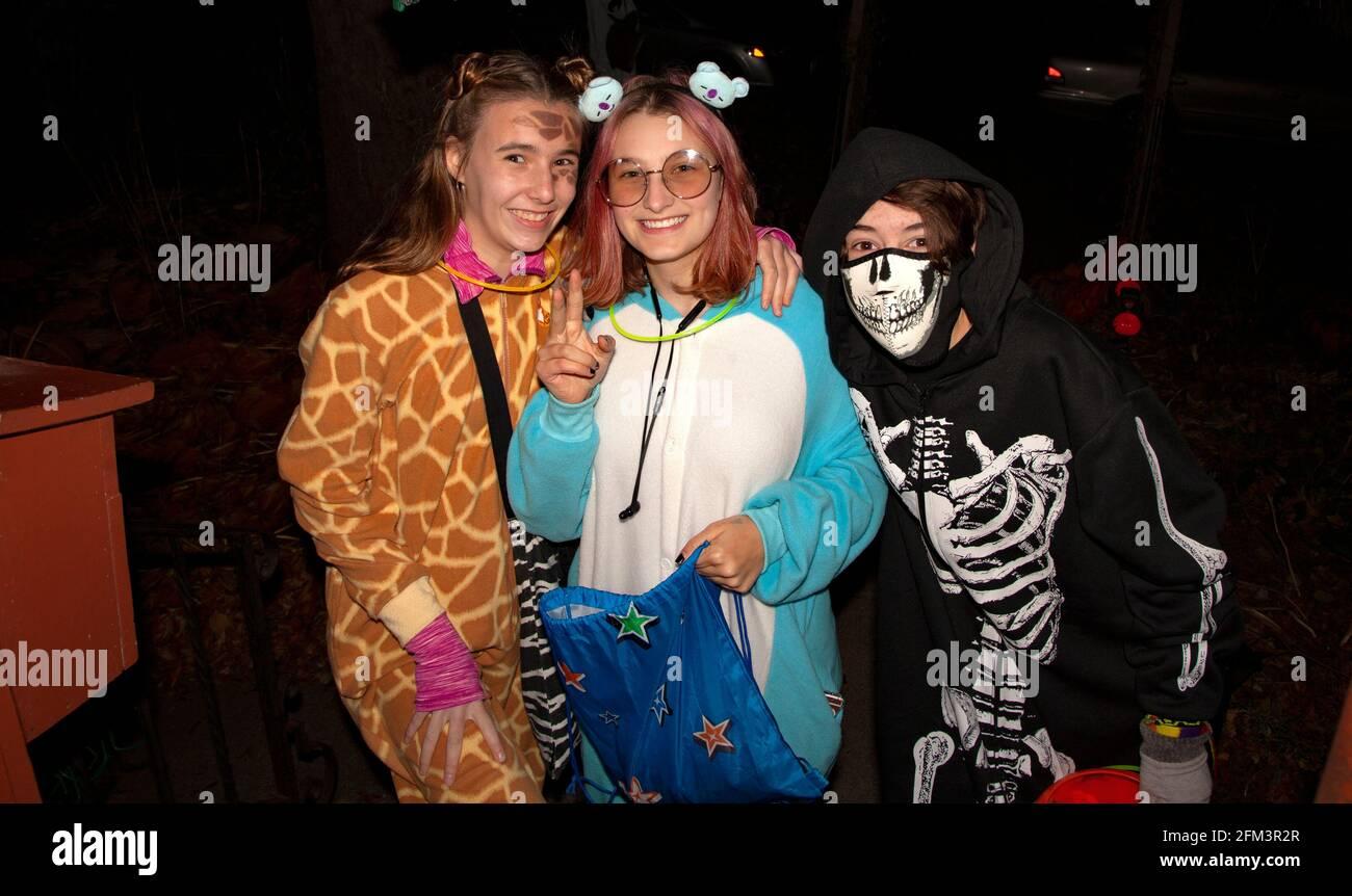 Halloween trampear y tratar a las adolescentes disfrazadas como jirafa, criatura del espacio exterior, y esqueleto. St Paul Minnesota MN EE.UU Foto de stock