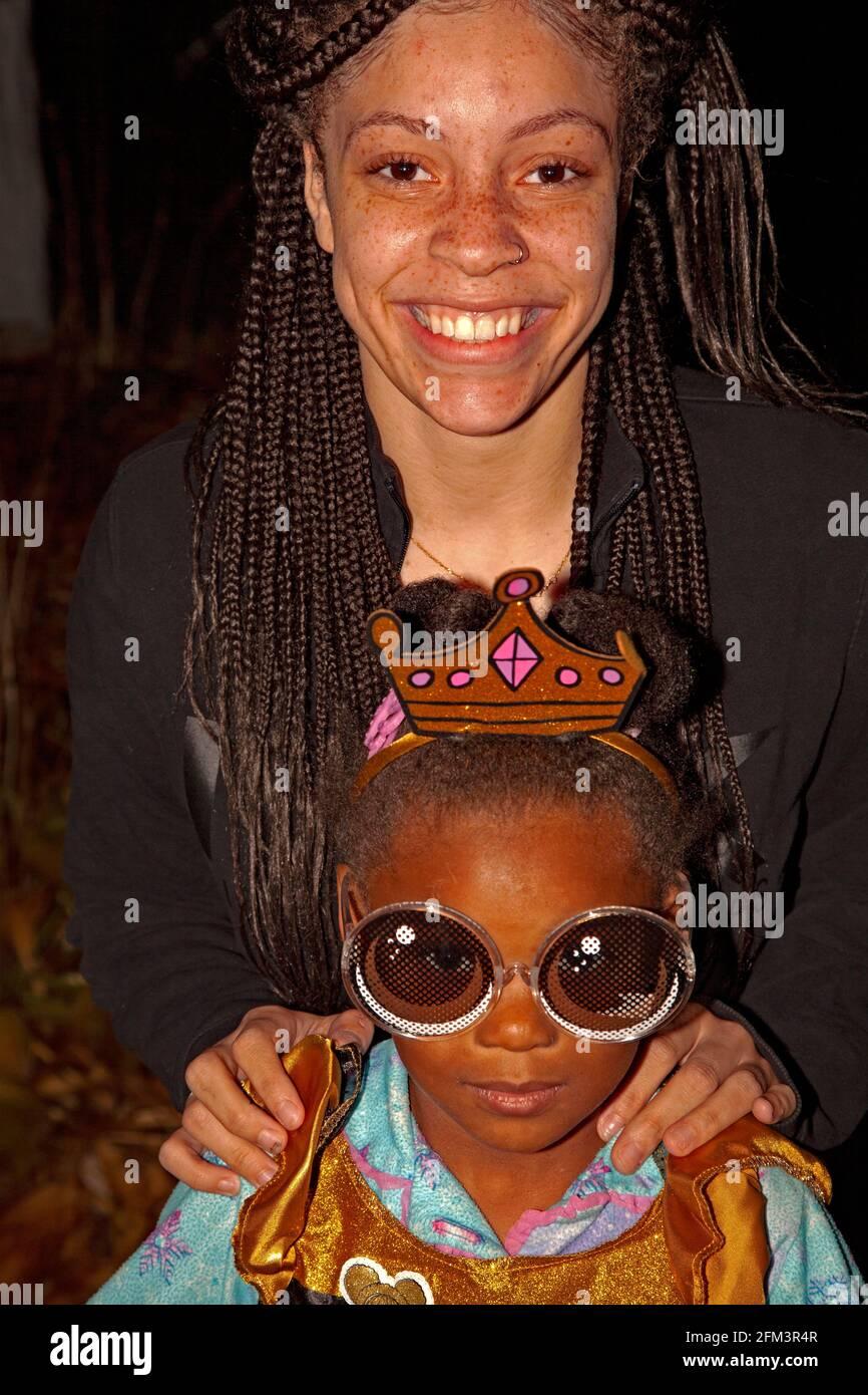 Truco de Halloween o el tratador disfrazados como una princesa usando grandes gafas de sol con mamá sonriendo detrás de ella. St Paul Minnesota MN EE.UU Foto de stock