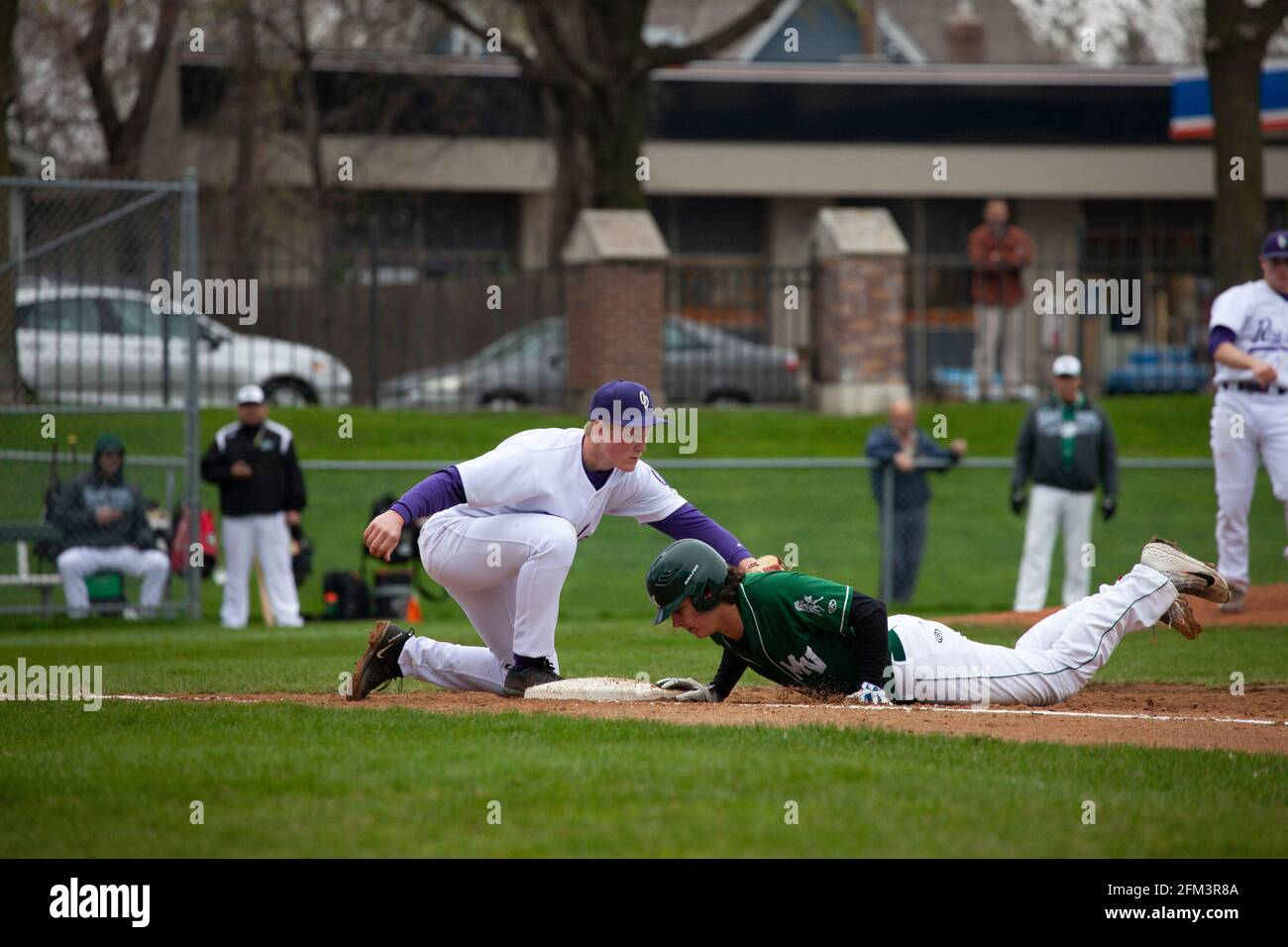 El jugador de béisbol deslizando la cabeza hacia la base y el jugador tratando de marcarlo en el Cretin Durham Hall Field. St Paul Minnesota MN EE.UU Foto de stock