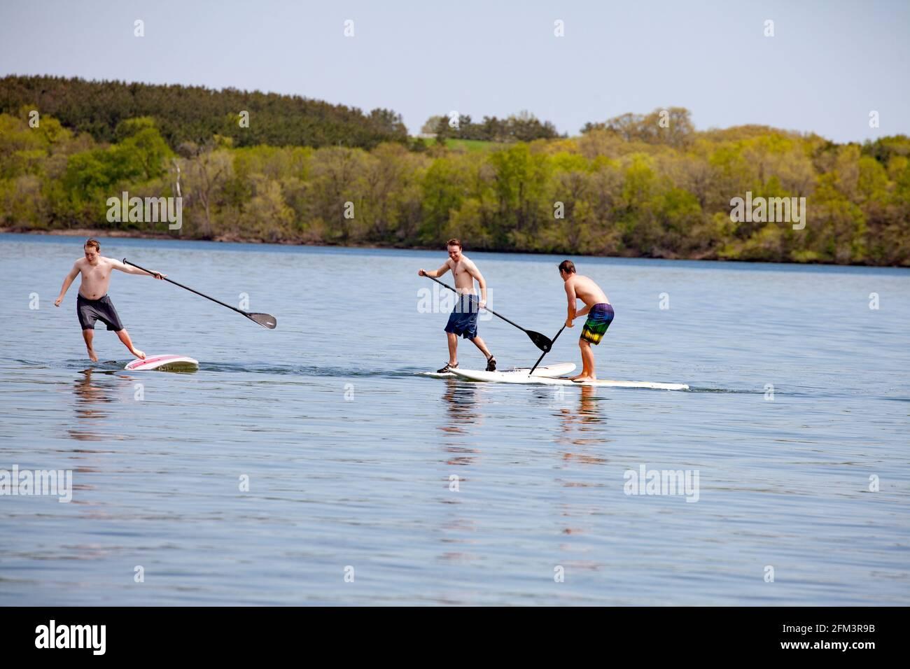 Tres adolescentes retozando juntos en tablas de remo en el tranquilo lago Clitherall. Clitherall Minnesota MN Estados Unidos Foto de stock
