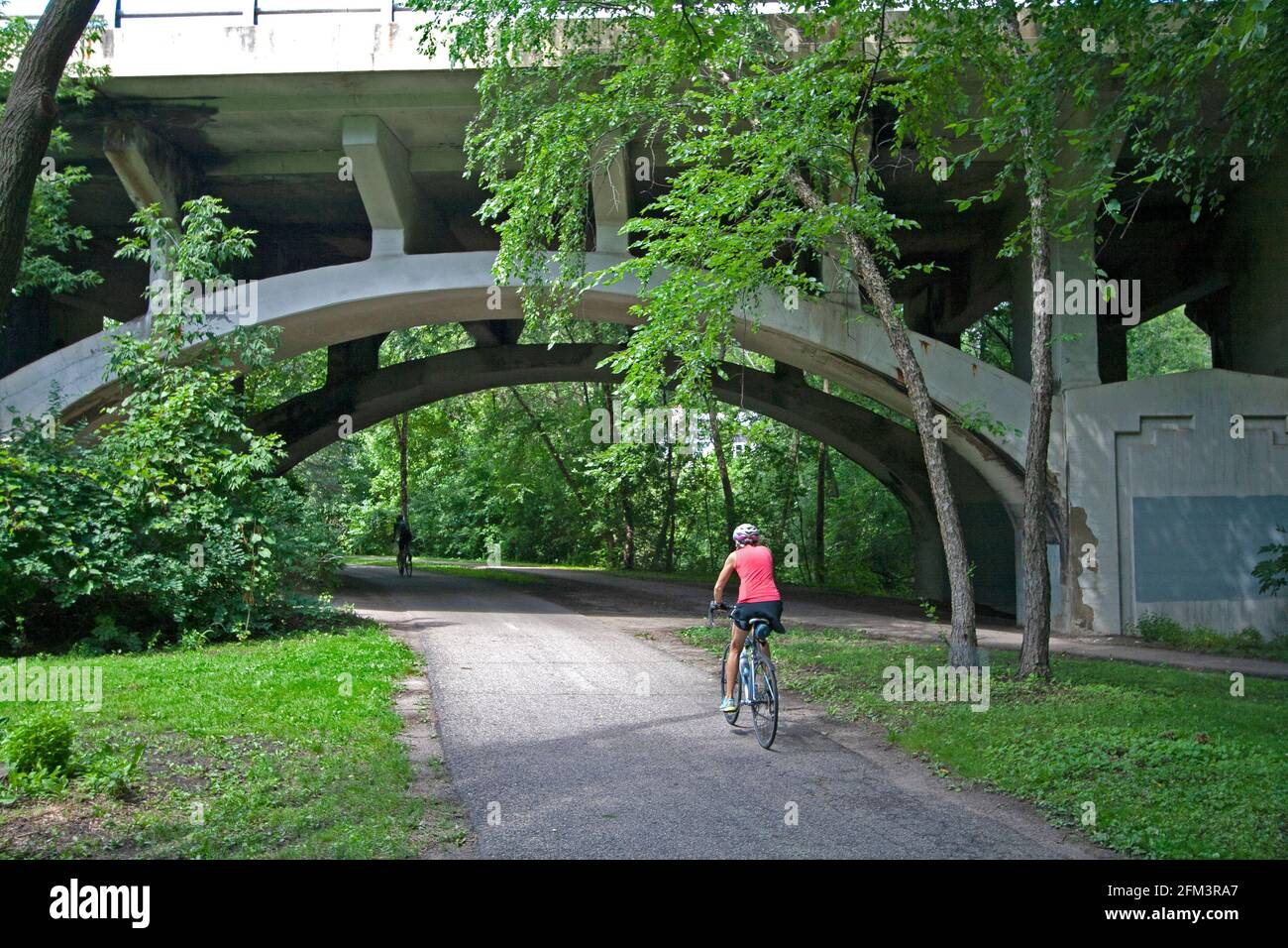 Ciclistas pedaleando a lo largo de la ruta regional Minnehaha Parkway a punto de pasar bajo el arco del puente de la avenida Nicollet. Minneapolis Minnesota MN Estados Unidos Foto de stock