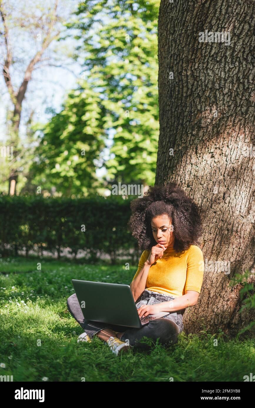 Mujer afro hermosa mecanografiando en un ordenador portátil en un jardín. Foto de stock