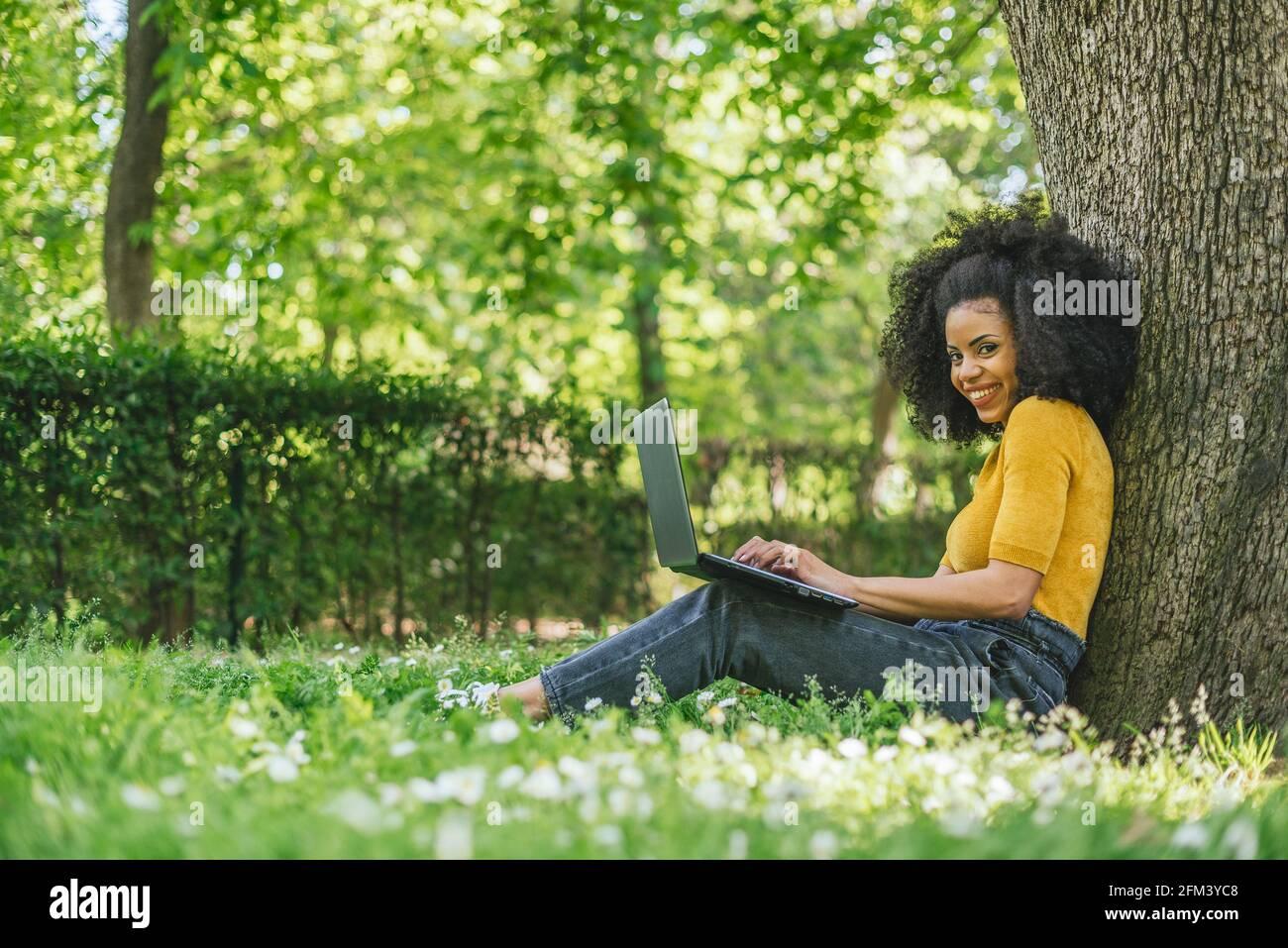 Mujer afro hermosa y feliz mecanografiando en un ordenador portátil en un jardín. Foto de stock