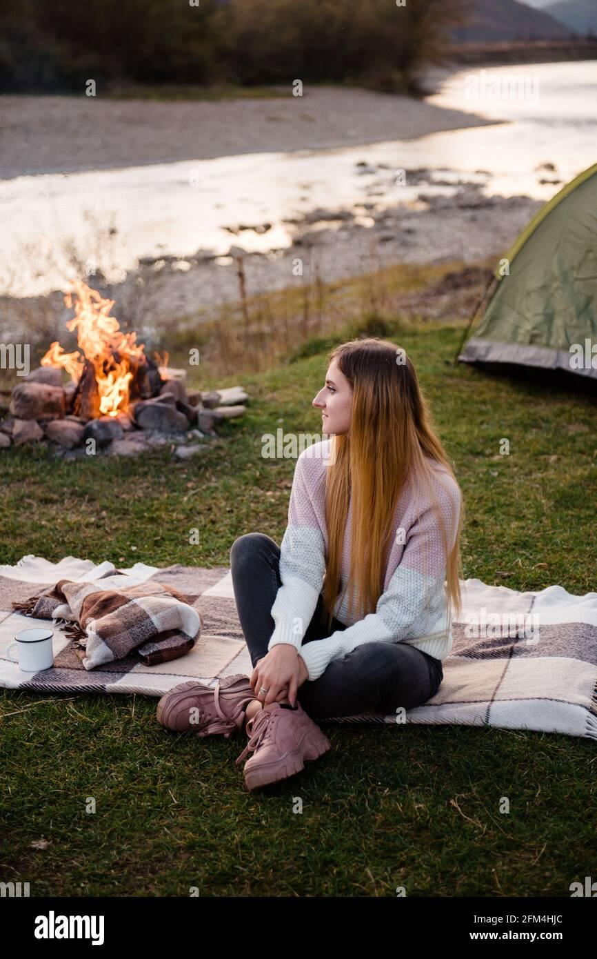 Descanse cerca de las montañas. Por la tarde, la joven se sienta cerca de una tienda y disfruta de las vistas a la montaña. La fogata está iluminada en el lado. Foto de stock