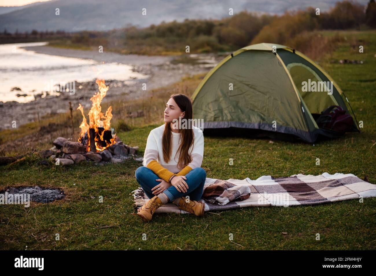 Vista frontal de la joven morena por la tarde se sienta cerca de una tienda y goza de vistas a la montaña. La fogata está iluminada en el lado. Camping y senderismo en el m Foto de stock
