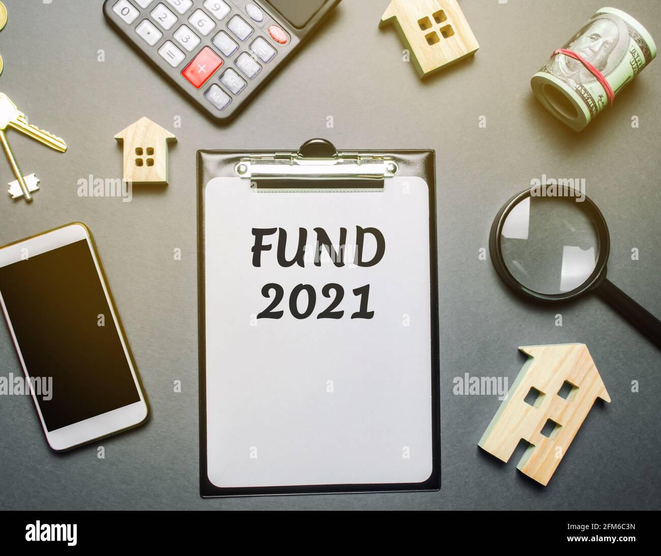 Notas con las palabras FONDO 2021, casas de madera, dinero y teléfono. Concepto de inversión inmobiliaria. Proyectos, construcción y explotación de bienes raíces ob Foto de stock