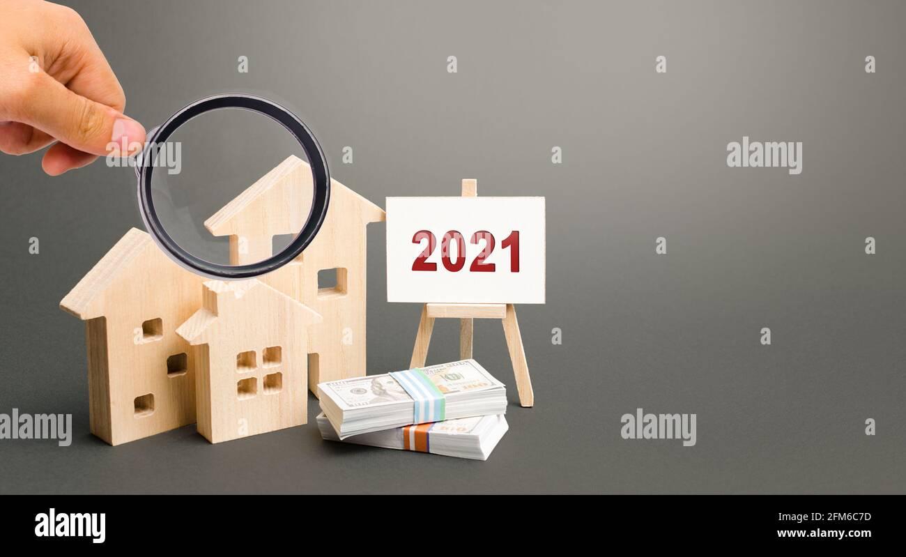 Inscripción 2021 y casas en miniatura. Concepto de bienes raíces. Planificación del presupuesto familiar. Inversiones, planes, ahorros. Tasas hipotecarias e hipotecarias. Previsión Foto de stock