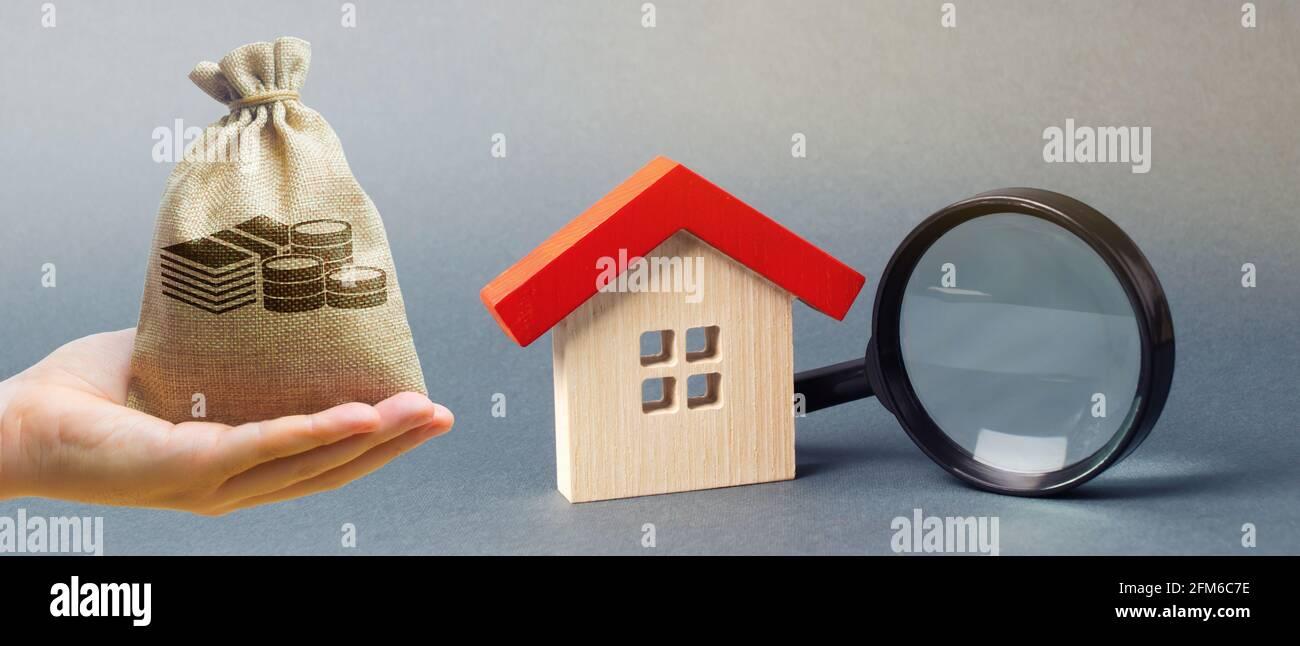 Bolsa de dinero, casa en miniatura y lupa. Valoración en casa. Valoración de la propiedad. Elección de ubicación para la construcción. Concepto de búsqueda de casas. Foto de stock