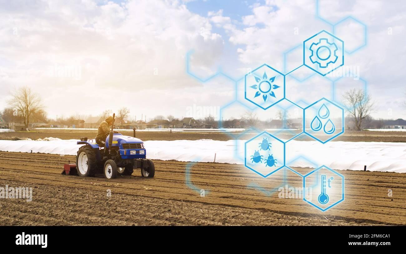 El agricultor en un tractor con fresadora afloja, muele y mezcla el suelo. Startups agrícolas, mejoras, digitalización de la industria agrícola. Inn Foto de stock