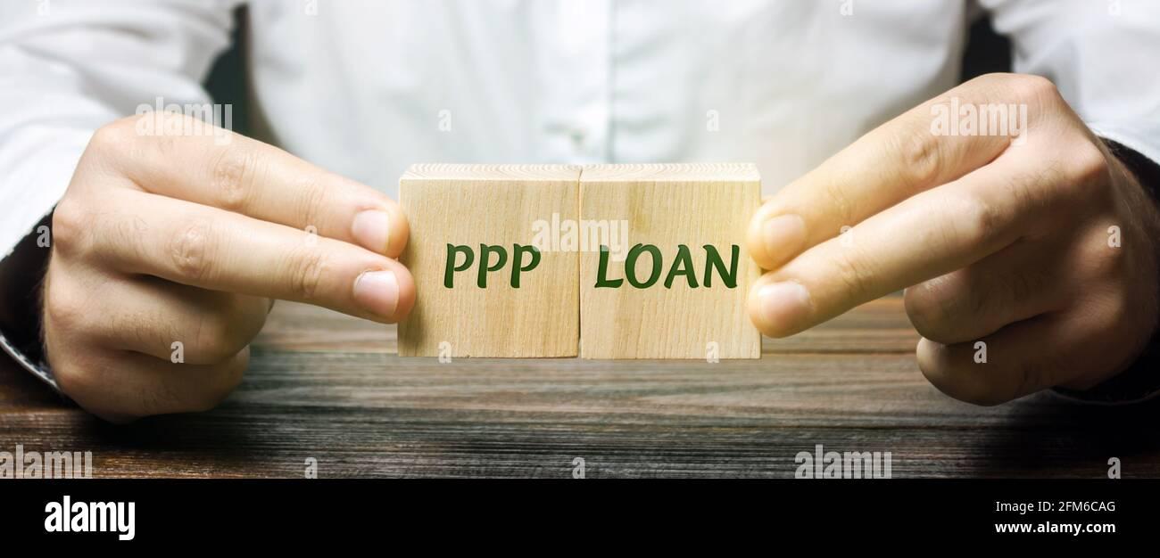 Businessman pone bloques con palabras PPP LOAN - PAYCHECK Protection Program. Préstamo diseñado para proporcionar un incentivo directo para que las pequeñas empresas mantengan el Th Foto de stock