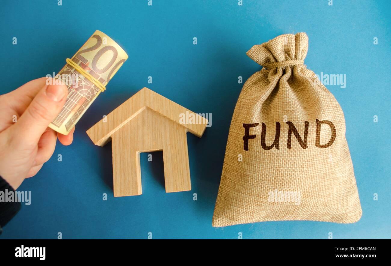 Bolsa de dinero con la palabra Fondo, casa de madera y billetes de euros en la mano. Concepto de inversión inmobiliaria. Proyectos, construcción y explotación inmobiliaria Foto de stock