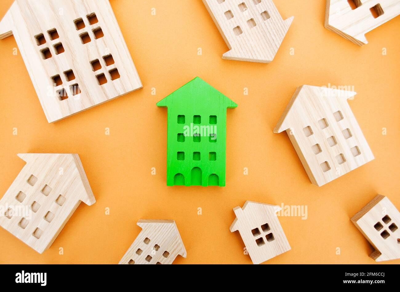 Muchas casas de madera en miniatura. Concepto de bienes raíces. Elija una vivienda asequible. Comprar y vender viviendas. Análisis de mercado. Demanda de vivienda. En aumento Foto de stock
