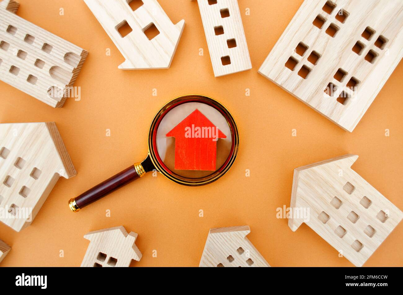 Lupa y casas de madera. Casa buscar concepto. Inicio evaluación. Valoración de Inmuebles. Elección de la ubicación para la construcción. Búsqueda de h Foto de stock