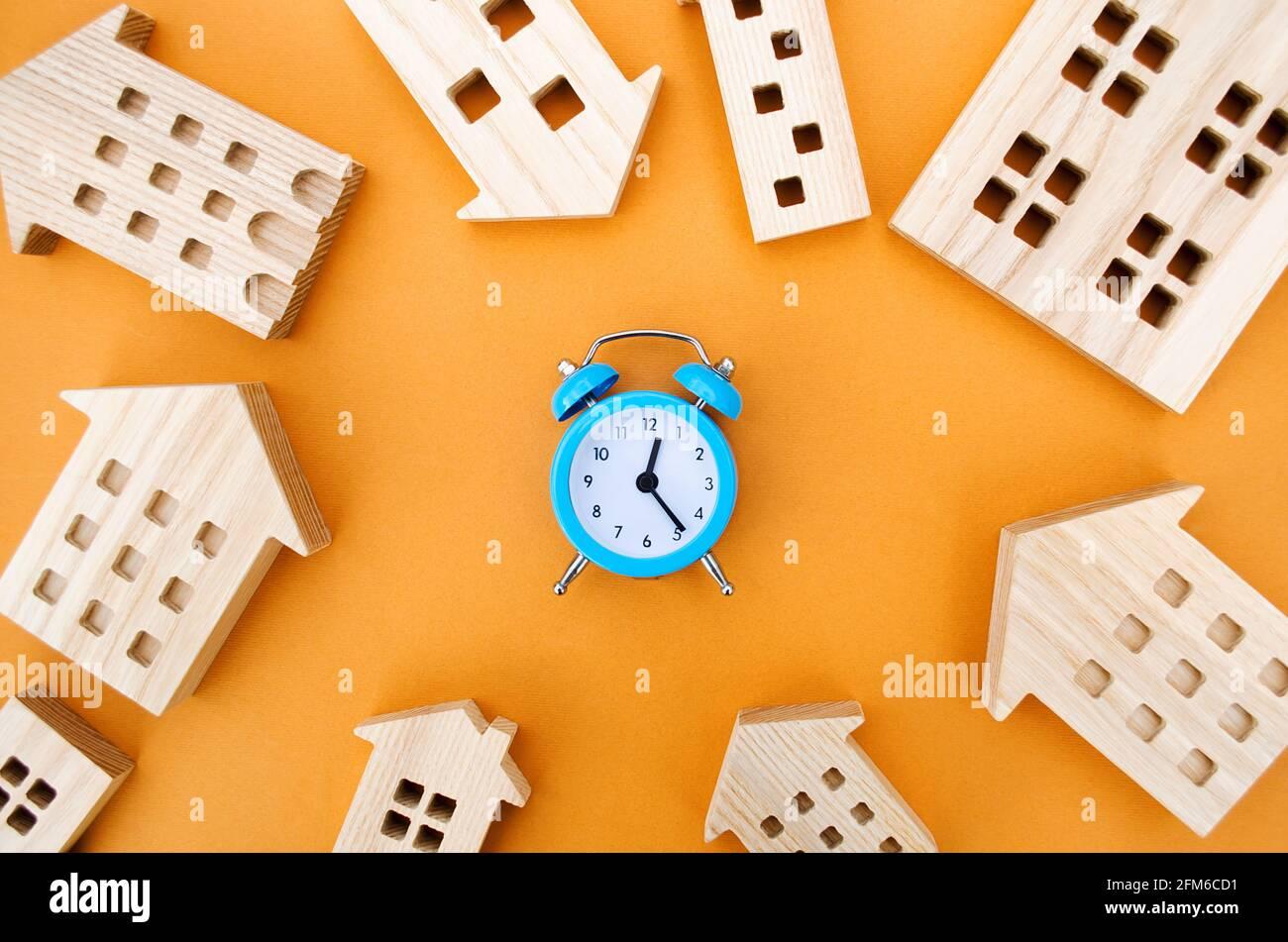 Un reloj despertador azul y muchas casas de madera alrededor. Concepto de hipoteca y préstamo. Bienes raíces y riesgos. Seguro de propiedad. Crédito. Pago de impuestos. Utilidades Foto de stock