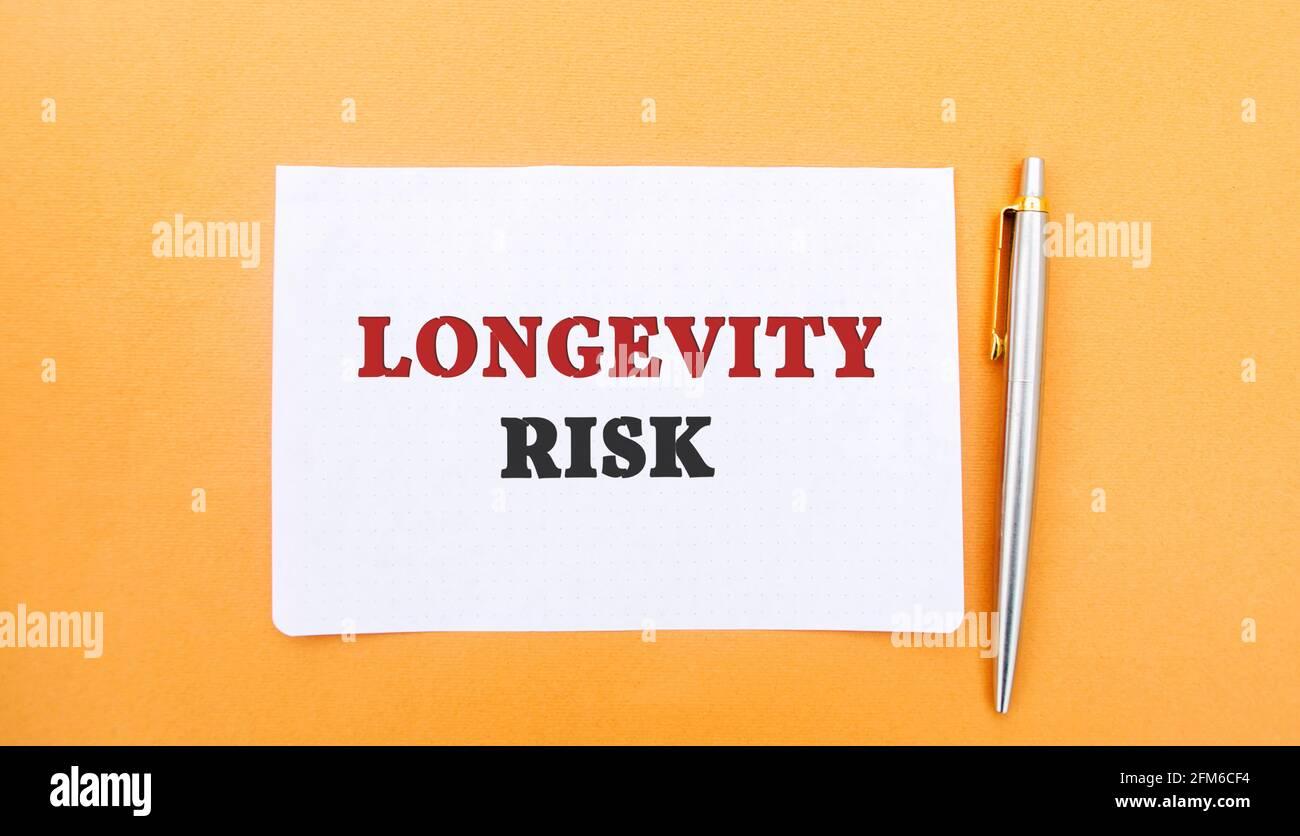 Una nota con la inscripción Longevity Risk y una pluma. Riesgo a largo plazo. Fondo de pensiones. Compañías de seguros. Riesgo de que las personas vivan más tiempo que curr Foto de stock