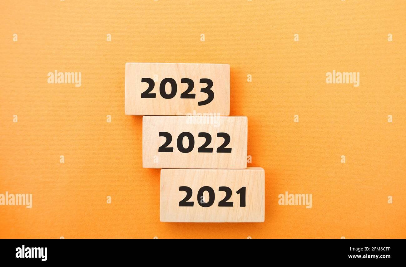 Bloques de madera 2021, 2022, 2023. El concepto del comienzo del nuevo año. Nuevos objetivos. Próxima década. Tendencias y cambios en el mundo. Crear planes y. Foto de stock