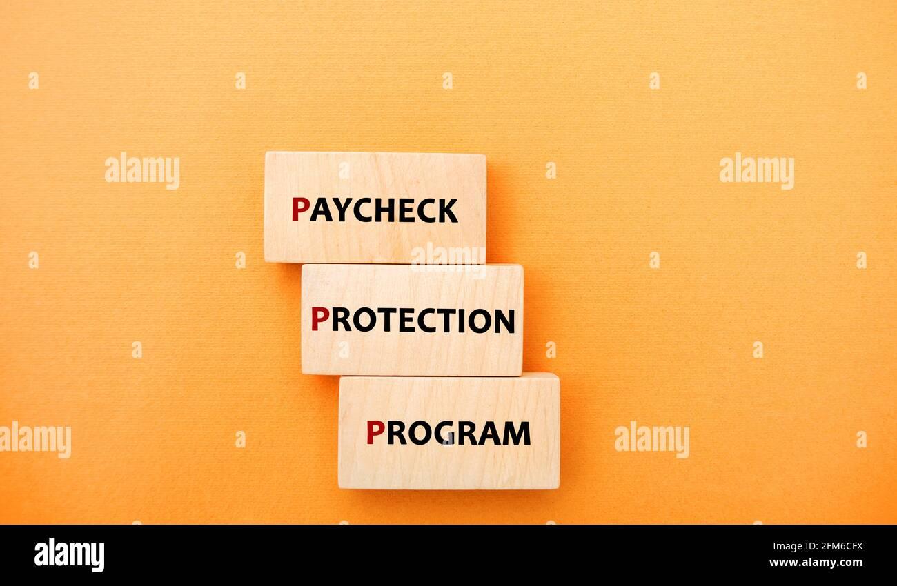 Bloques de madera con palabras Paycheck Programa de Protección. Préstamo que ayuda a las empresas a mantener a su fuerza laboral empleada durante la crisis de COVID-19. Negocios Foto de stock