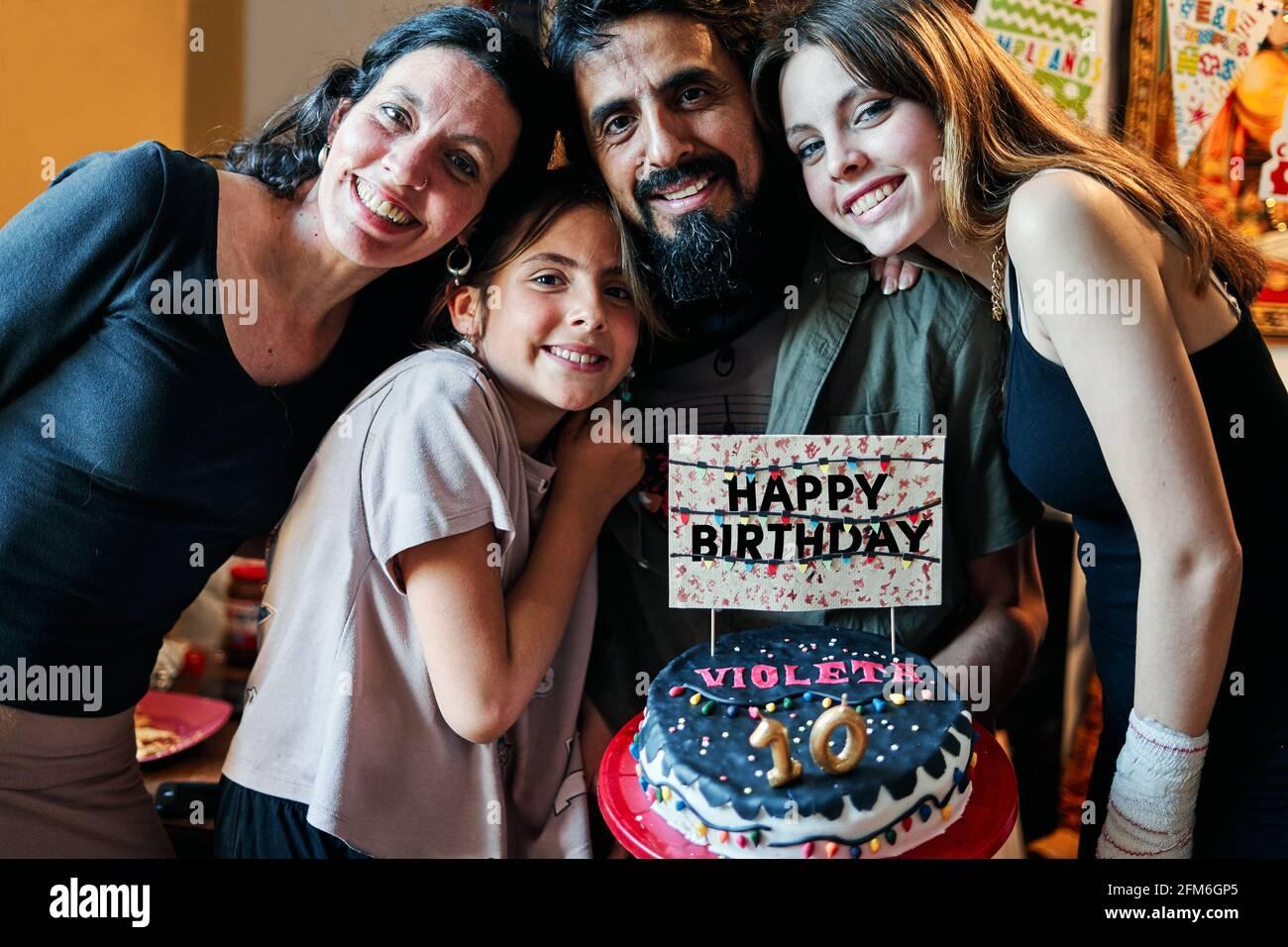 Retrato de una familia latina que celebra el cumpleaños de la niña de 10th años Foto de stock