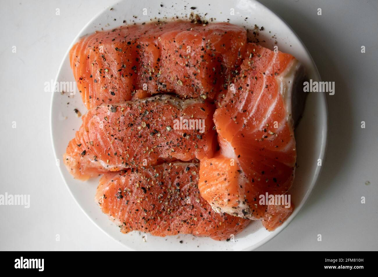 Apetitosos trozos de salmón crudo fresco con especias tumbadas un plato blanco Foto de stock