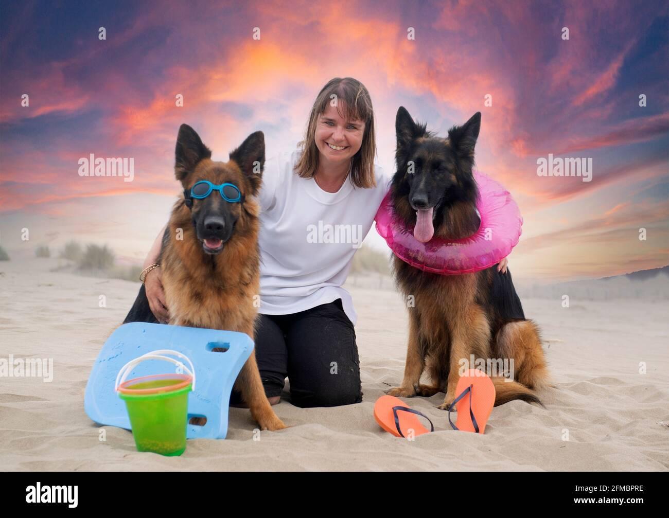 mujer y pastores alemanes se quedan en la playa Foto de stock