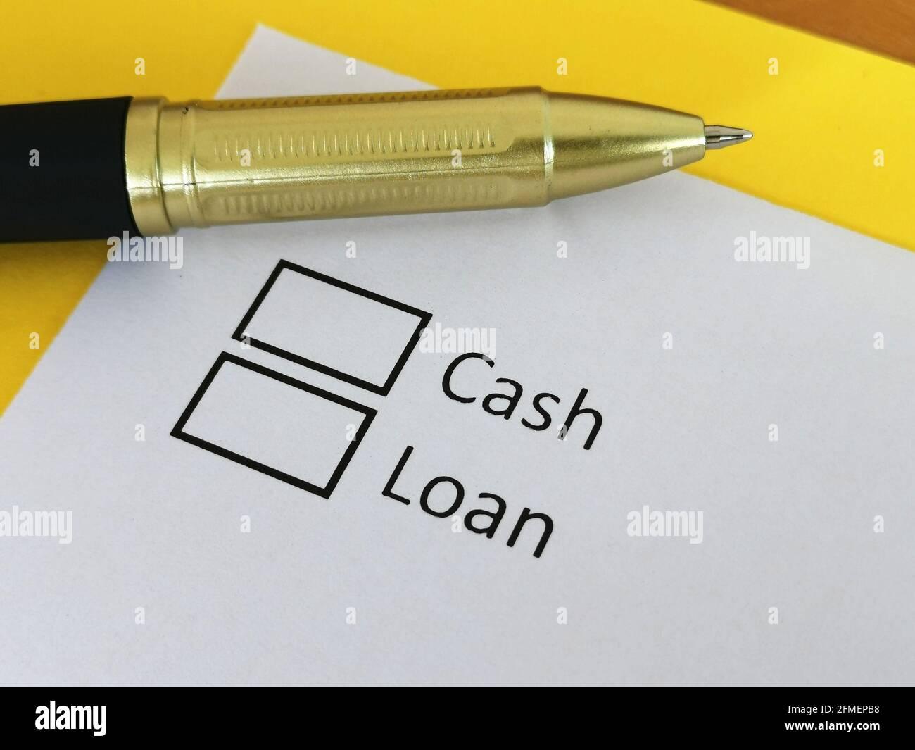Una persona está respondiendo a la pregunta acerca de comprar con dinero en efectivo o préstamo. Foto de stock